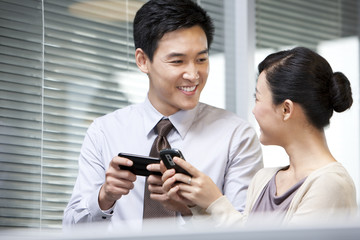 Young Businessman Smiling at Young Businesswoman