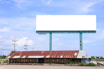 Blank billboard behind rusty roof of salt shed with blue sky for