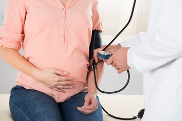 Doctor Checking Pregnant Woman's Blood Pressure