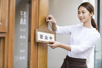 Young waitress with open sign in restaurant doorway