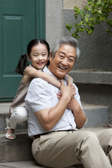 Chinese Grandfather and Grandaughter embracing on front stoop