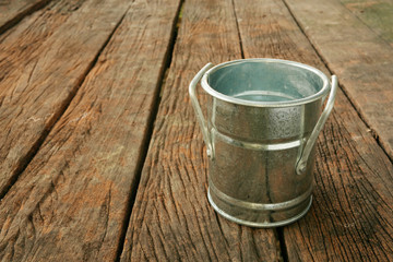 The small vintage zinc pot on the old dark brown wooden planks.