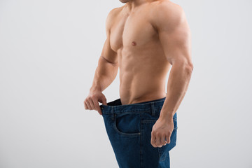 Muscular Man In Old Jeans Showing Weight Loss