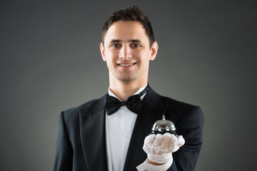 Smiling Waiter Holding Service Bell