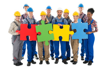 Confident Construction Workers Joining Jigsaw Pieces