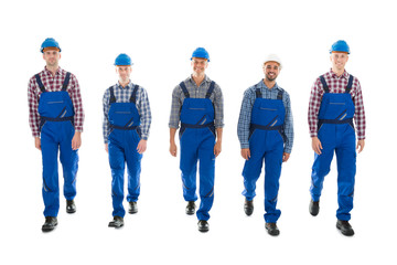 Portrait Of Confident Male Carpenters Walking In Row