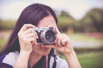 Female photographer with professional digital camera. Retro style