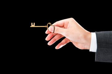 鍵を持っているビジネスマンの手,黒背景