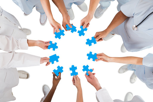 Medical Team Holding Blue Jigsaw Pieces In Huddle