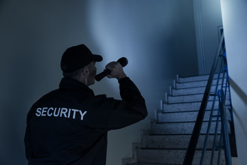 Security Guard Searching On Stairway With Flashlight