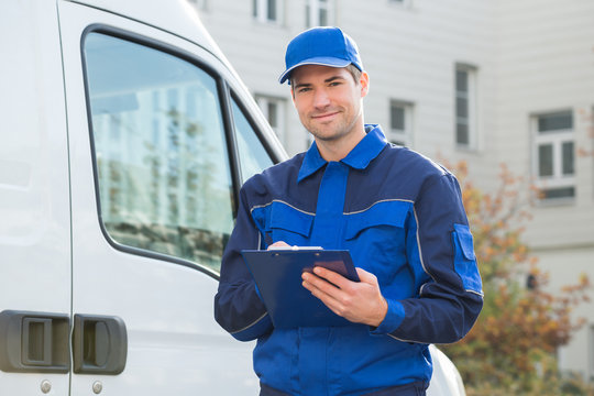 Delivery Man In Uniform Holding Clipboard By Truck