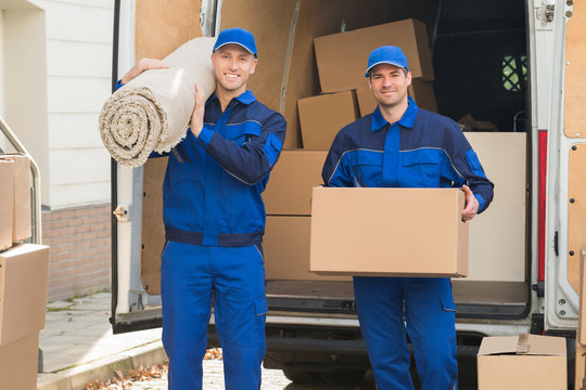 Happy Delivery Men Carrying Cardboard Box And Carpet