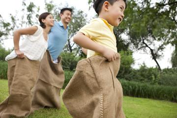 Cheerful family playing sack race