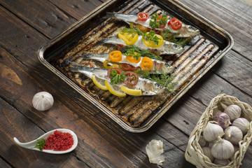 Cooking fresh herring fish with garlic lemon dill cherry tomatoes