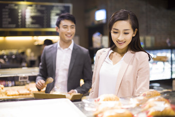 Young couple choosing breads in bakery