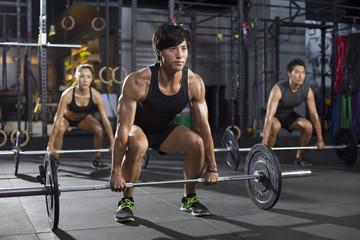 Young athletes lifting barbells at gym