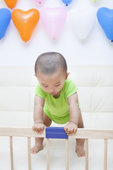 Chinese baby boy playing on a sofa