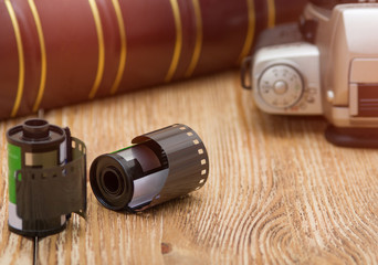 Old film camera and roll films on the wooden background. Low depth of field. Tinted image.