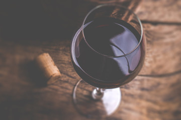 Red wine glass Tasting fine wine at dinnerm Tilt shift selective focus effect vintage style photo