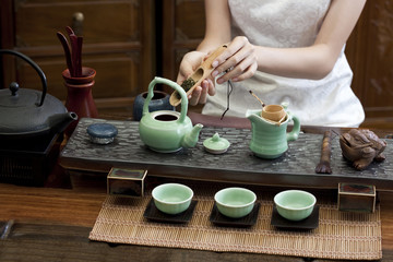 Young woman putting tea leaves into teapot