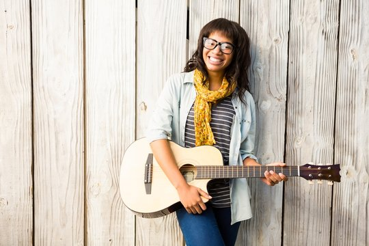 Smiling casual woman playing guitar