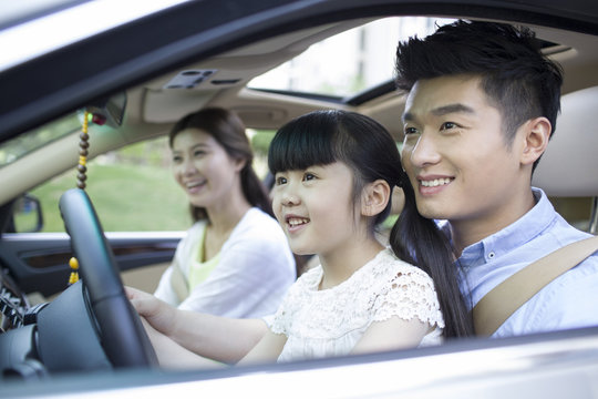 A happy family traveling in a car