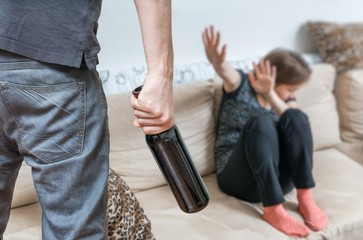 Woman is afraid of her alcoholic husband. Domestic violence concept.