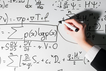 Man writing complex math formulas on whiteboard. Mathematics and science