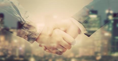 Double exposure of business people handshake on big city background