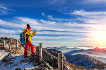 Young woman hiker taking photo with smartphone on mountains peak
