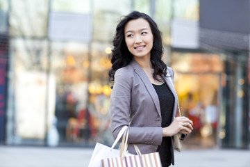 Smiling young woman holding shopping bags while walking