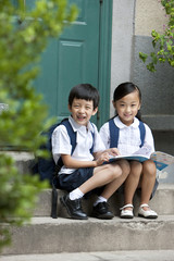 Two school children studying outside