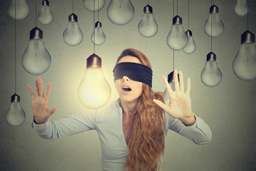 Blindfolded young woman walking through lightbulbs searching for bright idea