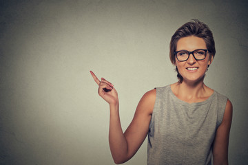 happy woman in glasses pointing with finger at blank copy space
