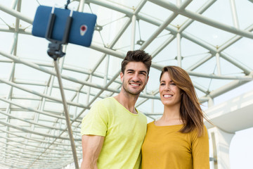 Young caucasian couple use selfie stick for taking photo togethe