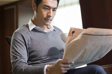 Young businessman reading newspaper in study
