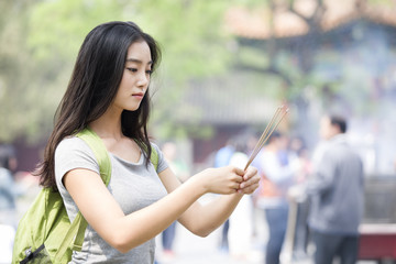 Young woman burning incense in the Lama Temple