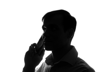 Portrait of a young man with a smartphone, tablet in hand - silhouette
