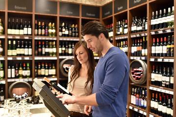 junges Paar kauft wein im Supermarkt ein - Produkinformation via moderner Technik // young couple buying wine in a supermarket - product information via modern technology
