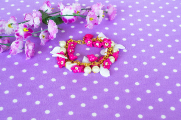 Colorful bracelet with beads and plastic flowers and leaves