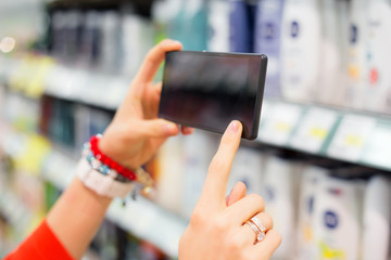 Woman in supermarket using mobile device