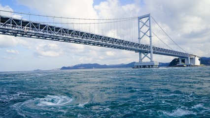 大きな渦を巻く鳴門海峡の渦潮と大鳴門橋