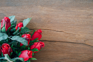 Valentine red roses on old wood background.