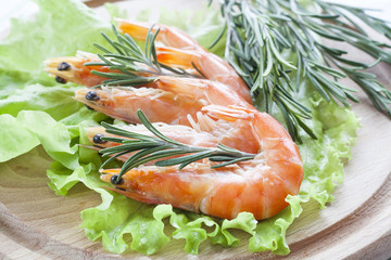 Tiger Prawn Shrimps with green lettuce and rosemary. Prawn Shrimps with green lettuce and rosemary on wooden board.