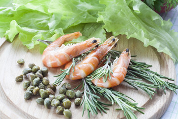 Tiger Prawn Shrimps with green lettuce, capers and rosemary. Prawn Shrimps with green lettuce, capers and rosemary on wooden board.