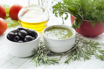Marinated black olive and homemade sauce mayonnaise in ceramic pots. Marinated black olive and homemade sauce mayonnaise in ceramic pots with parsley, rosemary and fresh tomatoes.