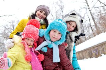 The company of cheerful happy children on winter walks