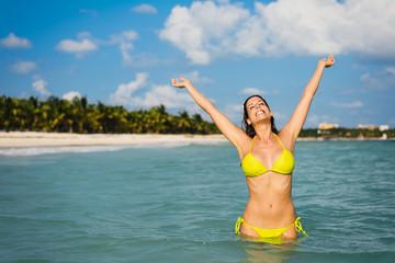 Beautiful sexy bikini girl enjoying relax and having fun into caribbean sea during summer vacation travel to Riviera Maya, Mexico. Blissful woman wearing yellow bikini and raising arms.