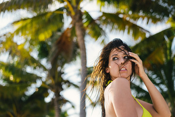 Sexy natural woman on tropical travel and beach vacation. Female brunette with wet wild hair portrait.