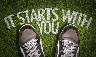 Top View of Sneakers on the grass with the text: It Starts With You